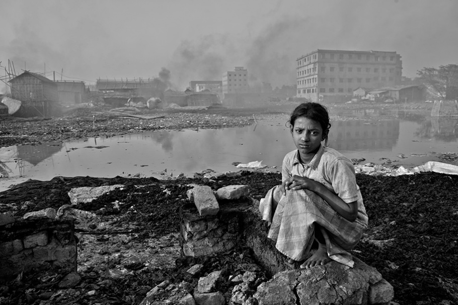 girl sitting in front of polluted water and buildings